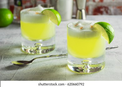 Two Pisco Sour Cocktails in Glasses with a Lime and Ingredients on the Bar