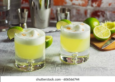Two Pisco Sour Cocktails with Ingredients and Bottles on a Bar