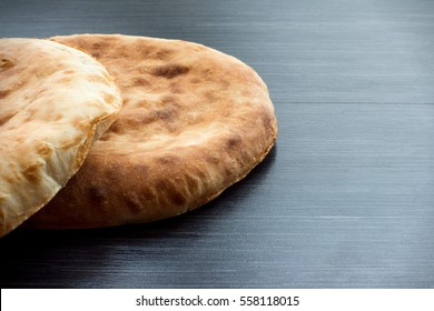 Two pita bread on wooden table.
