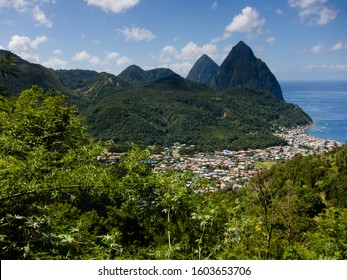The Two Pitons mountains named Gros Piton and Petit Piton on the coast of St Lucia with a blue ocean and the homes and houses of the island in foreground with forested hillsides - Image