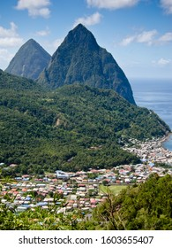 The Two Pitons mountains named Gros Piton and Petit Piton on the coast of St Lucia with a blue ocean and the homes and houses of the island in foreground with forested hillsides - Vertical Image