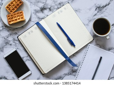 two planners on marble background, coffee, waffles and smartphone - buisness lunch