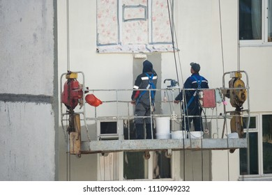Two plasterers, the painter perform painting on the facade of the building at the height of the building cradle. A view of the job of painting the wall from the back of the workers.