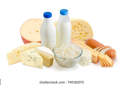 Two plastic bottles of milk, glass bowl of cottage cheese and several kinds of hard, semi-hard and soft cheese on a white background