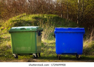 Two plastic garbage containers stand in the village against the backdrop of nature. one green, one blue