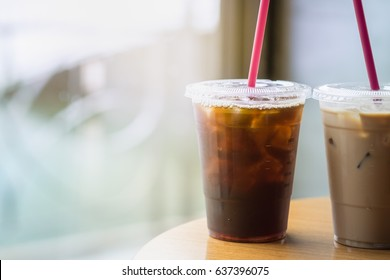 Two plastic take away cup of iced black coffee americano and iced coffee latte on wood table in coffee shop
