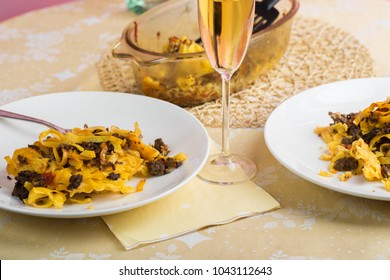 Two plates with baked pasta with beef and tomato, glass of vine and pan.