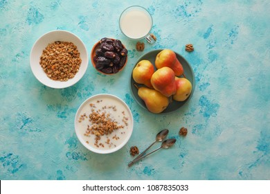 Two plates of muesli on a blue table. Muesli with dates and pears.
