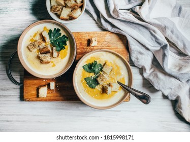 two plates of pumpkin soup next to greens pumpkin and bread croutons on a white wooden table top view close up