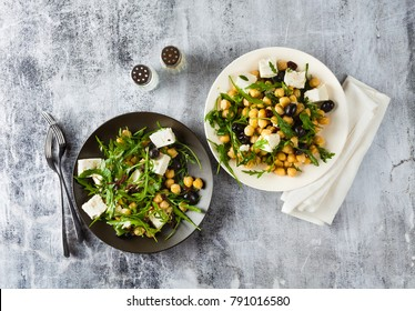 two plates of vegetable salad with chickpeas, arugula, feta cheese or tofu and black olives on a natural stone background. healthy eating
