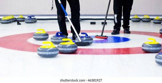 Two players with brooms on the ice, determining the strategy during a curling game