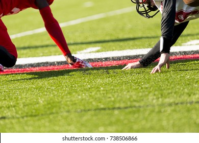 two players going after the football on the sidelines of the football field