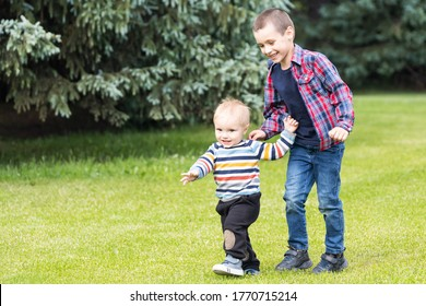 Two playful caucasian brother children enjoy having fun playing together at home backtard green grass lawn at summer day. Brother  happy childhood concept. Big brother helps younger brother to walk