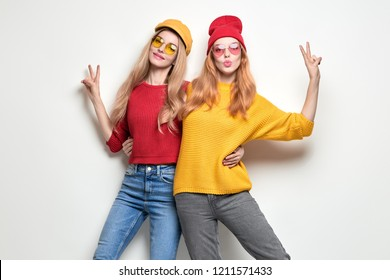 Two Playful Sisters Friends Having Fun, Kiss Face Expression, peace sign. Young Beautiful Hipster Girl in Stylish Jumper, Autumn Fashion Trendy Outfit. Woman Smiling, Happy positive emotion