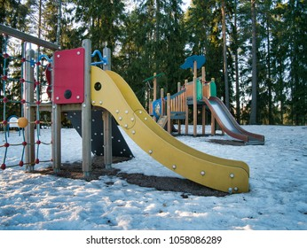 Two playground climbing frames with slides look like elepants faces. They are located in a playground with snow and trees on the background. The lightning is during a golden hour, very peaceful.