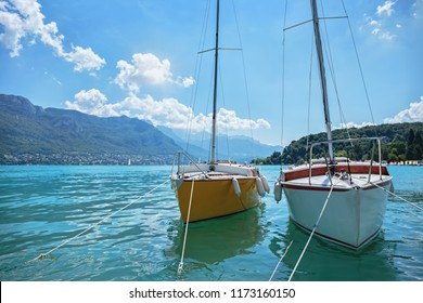Two pleasure yachts on the lake in the French city of Annecy in the background of the mountains.
