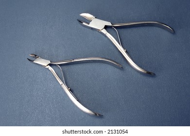 Two pliers on dark blue background from above