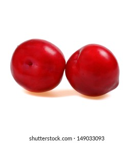 Two plums with shadows on white background