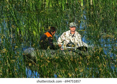 Two poachers on a rubber boat catch fish in the net. Zhitomir, Ukraine, June 16, 2017.