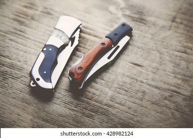 two pocket knife on wooden  table
