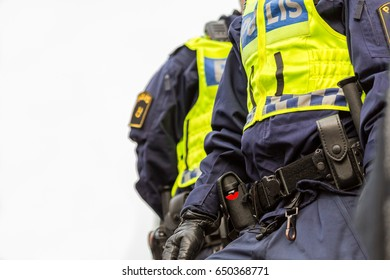 Two police officers, close up image from under of upper body with vest and equipment.