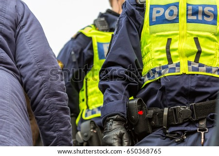 Two police officers in a crowd with yellow vests, close up of upper body with equipment belt.