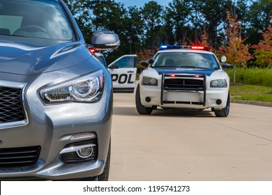 Two police vehicles stop a sedan on a routine traffic stop