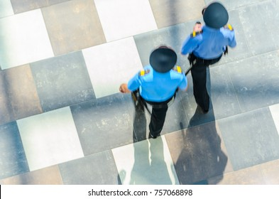 Two Policemen  in Blue Uniform Patrolling the Area, Top View.  Abstract Background. Motion Blur. Long Exposure