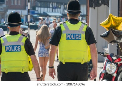 two policemen of different heights on the beat in the uk following a pretty girl with long legs and blonde hair