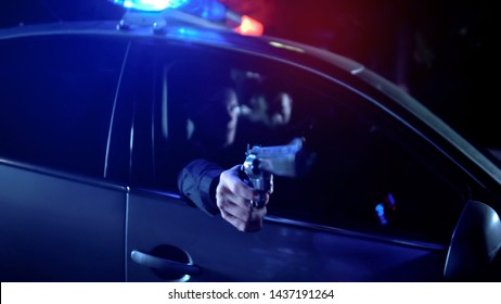 Two policemen sitting in patrol car at night and threatening criminal with guns