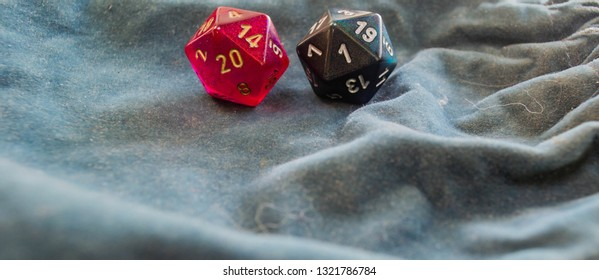 Two polyhedral d20 game dice exhibiting a 20 and a 1