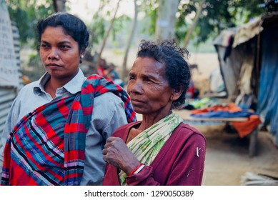 Two poor and adult women standing together wearing traditional dress
