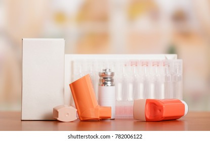 Two portable inhaler with dispenser and a box of ampoules on light background