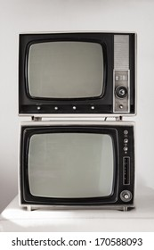 Two portable vintage televisions on white background