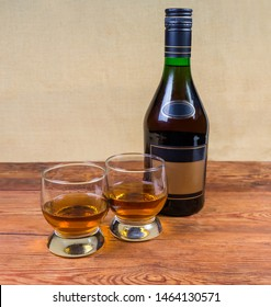 Two portions of brandy in brandy bowls and bottle of brandy on the old wooden rustic table