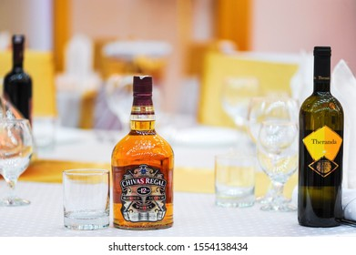 Two portions of brandy in brandy bowls and bottle of brandy on a textile surface