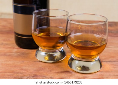 Two portions of brandy in brandy bowls on a background of brandy bottle on the rustic table in selective focus