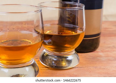 Two portions of brandy in brandy bowls on a blurred background of bottle of brandy on the rustic table close-up in selective focus