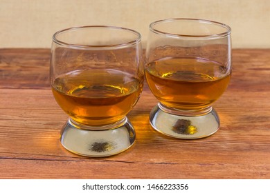 Two portions of brandy in brandy bowls on rustic table