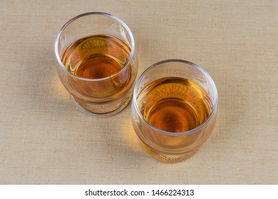 Two portions of brandy in brandy bowls on the textile tablecloth close-up, top view