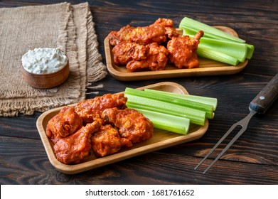 Two portions of buffalo wings with fresh celery stalks and blue cheese dip
