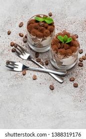 two portions Classic tiramisu dessert in a glass on concrete background