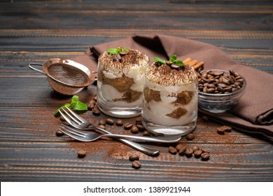 two portions Classic tiramisu dessert in a glass on wooden background