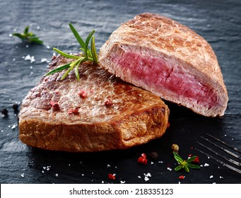 Two portions of lean trimmed grilled beef steak cut through to show the succulent tender red meat and seasoned with rosemary, salt and pepper in a steakhouse or restaurant