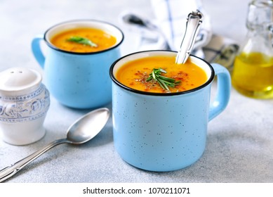 Two portions of pumpkin creamy soup in a blue emamel mugs on a light slate or concrete background.