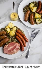 Zwei Portionen traditioneller deutscher Oldenburger Grünkohl mit geräuchertem Wurstmix, Kassler Schweinehacken, Senf und gekochte Kartoffeln