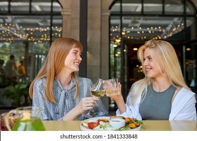 two positive caucasian women enjoy spending time together in restaurant, blonde females have talk and drink beverages, enjoy meal. they haven't seen each other for a long time