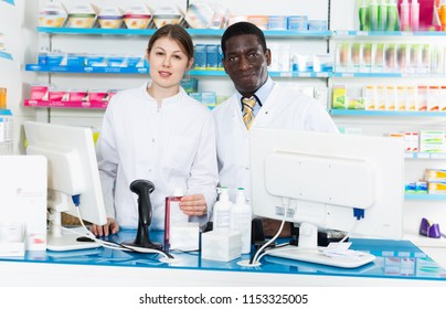 Two positive  confident pharmacists standing on background with shelves of medicines in pharmacy