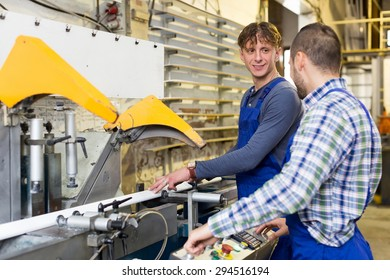 Two positive employes do his job on a machine in PVC shop