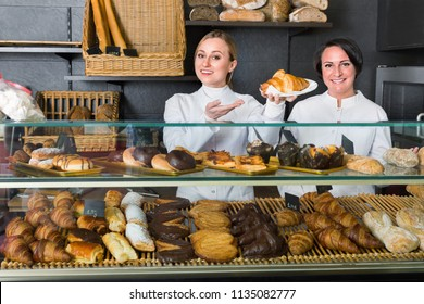 Two positive  female cooks demonstrating and selling pastry in the cafe counter